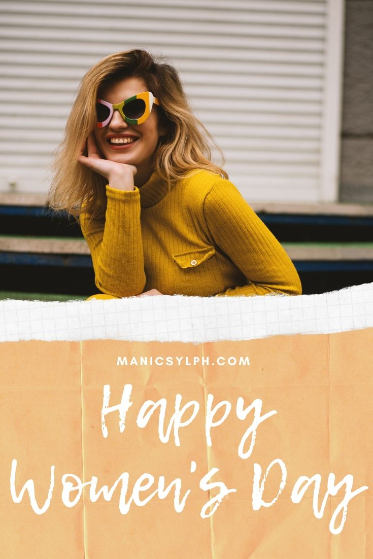 A smiling woman wearing a yellow sweater, with Happy Women's Day written on the picture