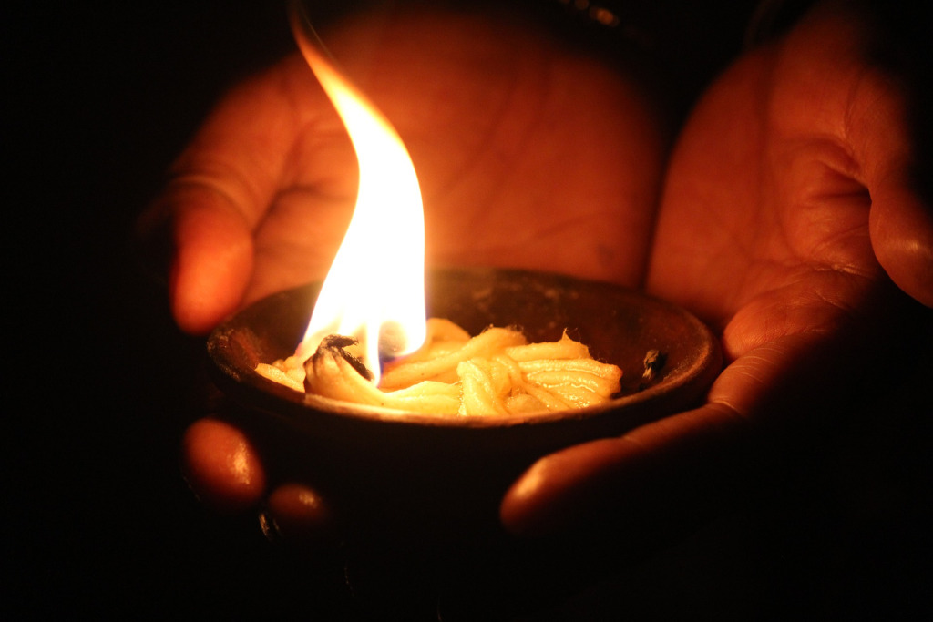 A hand holding a lighted earthen lamp